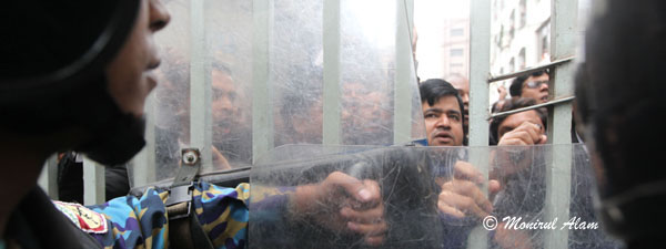 DEC 11 2012-Dhak, Bangladesh- Bangladeshi police stand guard and BNP lawyers shout slogan in form of CMM court during the Hortal hour.BNP and its close ally Jamaat-e-Islami observed dawn-to-dusk nationwide strike on Tuesday. They are demanding restoration of the caretaker government system. © Monirul Alam