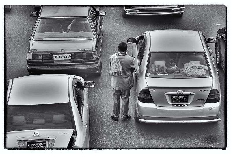 A private car owner stand still on the road and try to watch, what is happening during the long      traffic jam on the busy road in a frame gate area. The capital's messy traffic management system is manually handling around 3,000 traffic polices round the clock. ©Monirul Alam