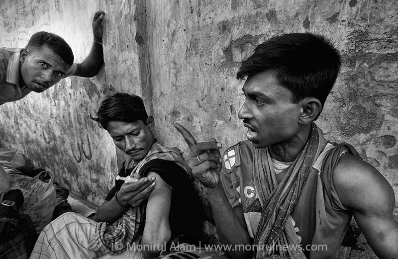 A group of drag addicts taking injecting drugs in open view of the public of a pedestrian overpass in Dhaka near the dhaka Medical College Hospital. © Monirul Alam