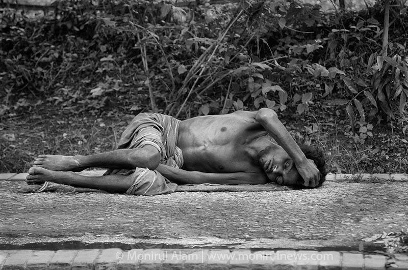 An addict sleep on the street at Agargaon in day time where  the public overpass him. Agargaon Dhaka. © Monirul Alam