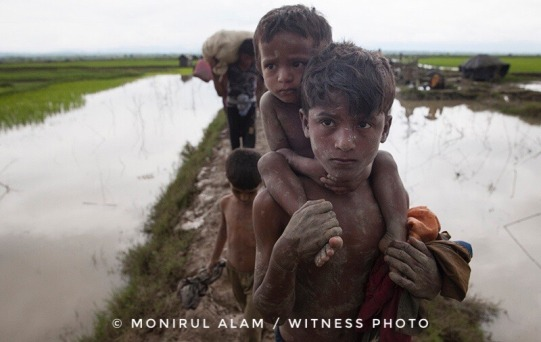 September 08, 2017 Takenuf, Bangladesh - Rohingya people, fled from ongoing military operations in Myanmar's Rakhine state, make their way through muddy water after crossing the Bangladesh-Myanmar border in Teknuf, Bangladesh on September 2017.
